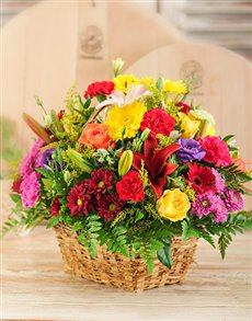 A woven flower basket with lilies, roses, gerbera's and sprays
