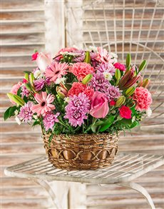Arrangement of pink flowers in a woven basket