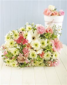 Arrangement of pastel coloured seasonal flowers in cellophane