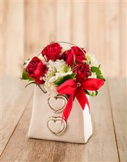 This handbag filled with sprays and red roses fini
