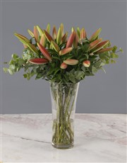 A tall glass vase with stargazer lilies completed