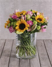 Bright Mix of Sunflowers in a Large Glass Vase
