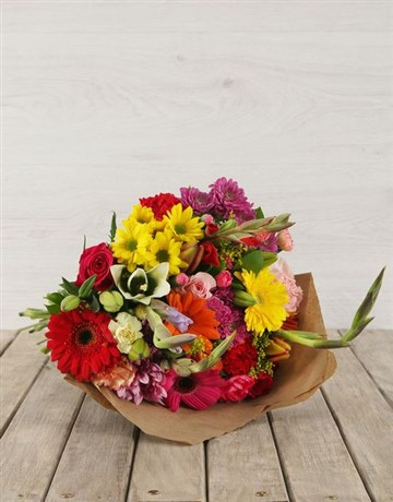Bouquet of mixed seasonal bright flowers in cellophane