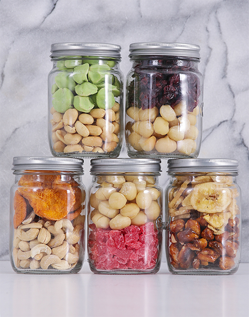 Five glass jars are stacked up against each other to form a pyramid. Inside each of the jars colourful combinations of dried fruit and nuts.